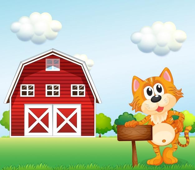 Kot trzyma pusty szyld ze stodołą z boku