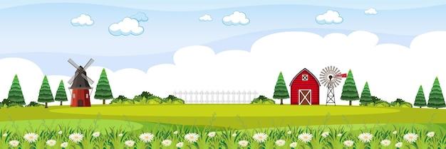 Krajobraz gospodarstwa z czerwoną stodołą i wiatrakiem w sezonie letnim