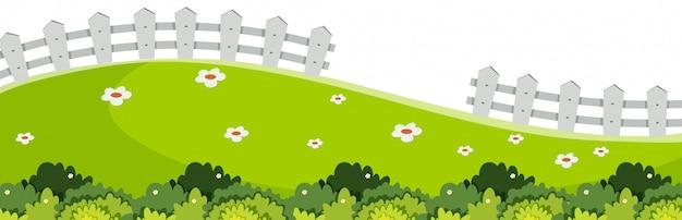 Krajobrazowy tło z zieloną trawą i bielu ogrodzeniem
