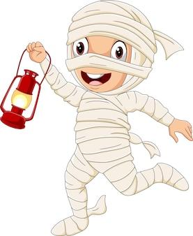 Kreskówka chłopiec ubrany w kostium mumii halloween, trzymając lampę
