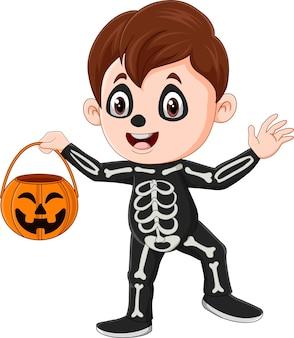 Kreskówka chłopiec ubrany w kostium szkieletu halloween, trzymający kosz z dyni