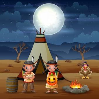 Kreskówka dzieci indian amerykańskich z tipi na pustyni w nocy