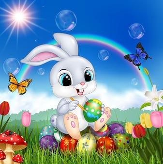 Kreskówka królik dekoruje wielkanocnego jajko