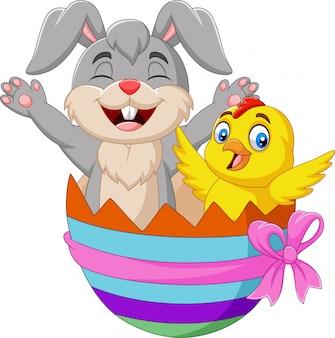 Kreskówka królik i dziecko kurczątko wśrodku wielkanocnego jajka