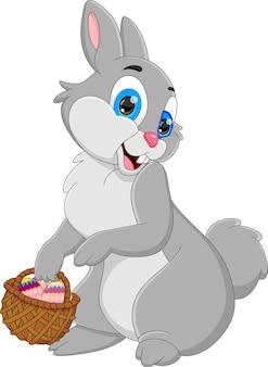 Kreskówka ładny królik trzymający kosz wypełniony jajkami