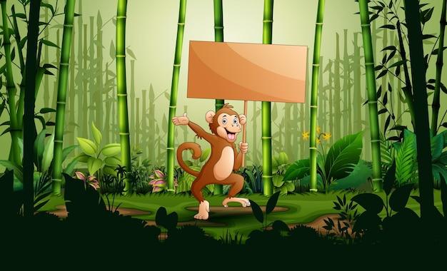 Kreskówka małpa trzyma drewniany znak w krajobrazie lasu bambusowego