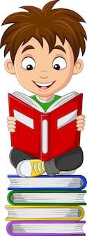 Kreskówka mały chłopiec czyta książkę na stosie książek