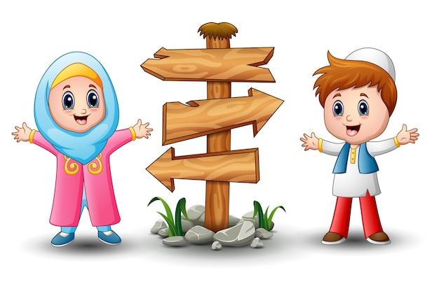 Kreskówka muzułmańskich dzieci z pustą znak strzałki drewna