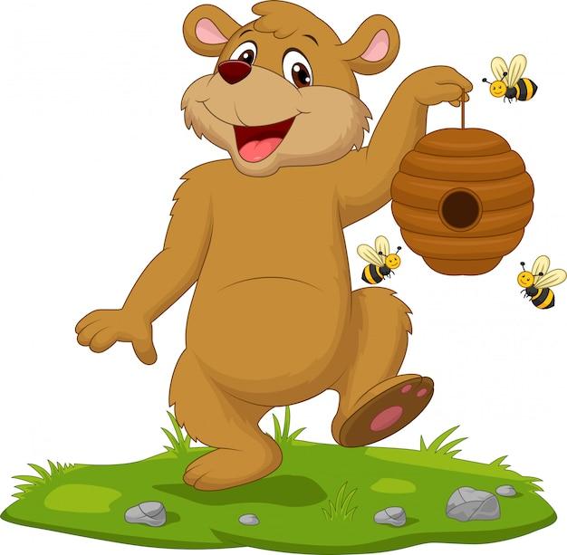 Kreskówka niedźwiedź trzyma ul na trawie