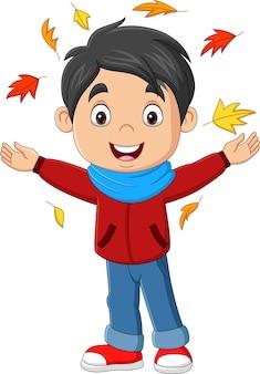 Kreskówka szczęśliwy chłopiec z jesiennymi liśćmi