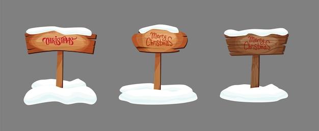 Kreskówka szyldy lub drewniane deski o różnych kolorach i fakturach ze śniegiem. wesołych świąt bożego narodzenia ręcznie napis tekst.