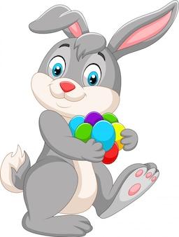 Kreskówka wielkanocny królik niesie kolorowych jajka