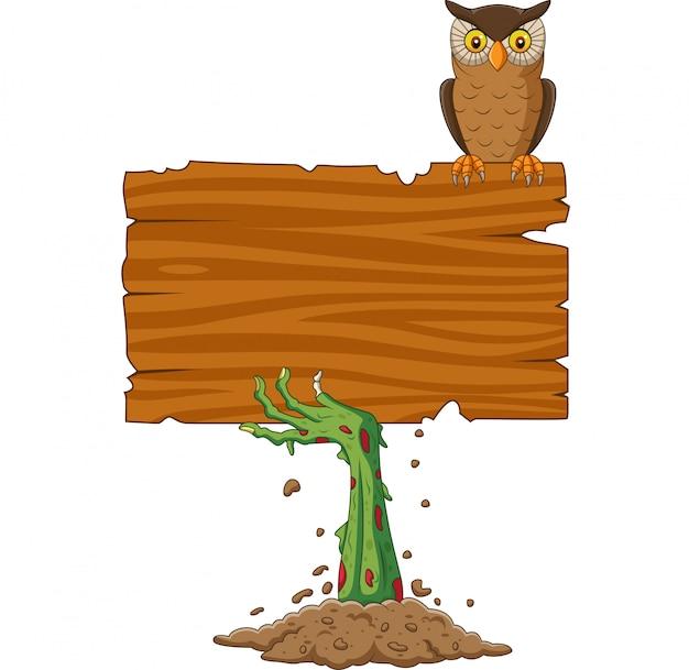 Kreskówka zombie ręka trzyma pusty znak z ptakiem sowa