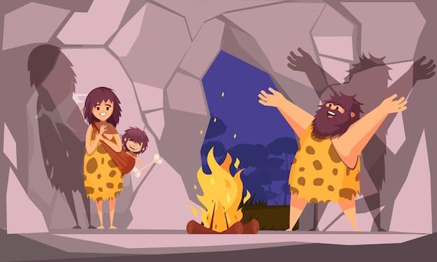 Kreskówki ilustracja z jaskiniową rodziną ubierającą w zwierzęcej skórce gromadzącej się wokół ogienia w jaskini