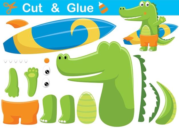 Krokodyl trzyma deskę surfingową. papierowa gra edukacyjna dla dzieci. wycięcie i klejenie. ilustracja kreskówka