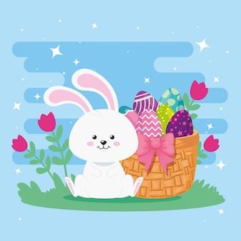 Królik z jajkami wielkanocnymi w wiklinowym koszu i dekoracji