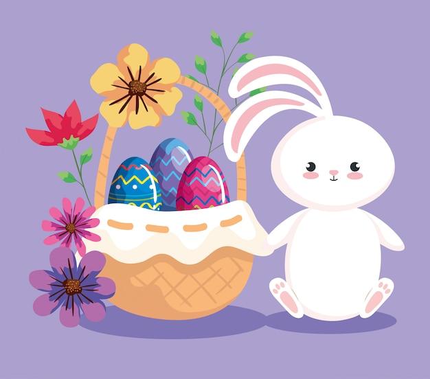 Królik z jajkami wielkanocnymi w wiklinowym koszu