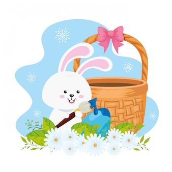 Królik z wiklinowym koszykiem i jajkiem wielkanocnym