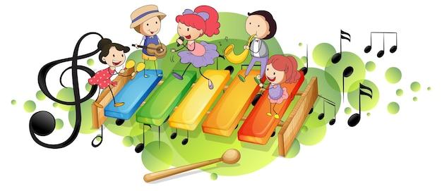 Ksylofon z wieloma szczęśliwymi dziećmi i symbolami melodii na zielonej plamie