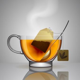 Kubek z przezroczystego szkła z torebką herbaty, łyżeczką i gorącą wodą