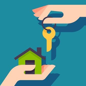 Kupno nowego domu. agent nieruchomości daje kupującemu brelok do domu.