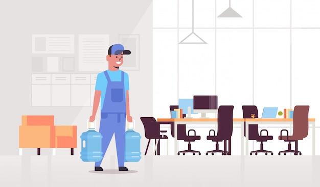 Kurier mężczyzna w mundurze niosąc dwie butelki słodkiej wody ekspresowej dostawy usługi koncepcji nowoczesne wnętrze biura