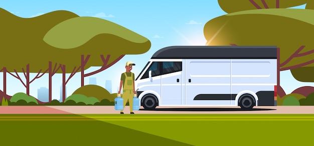 Kurier w mundurze trzyma dwie butelki świeżej wody ekspresowej dostawy usługi pojęcia mężczyzna blisko doręczeniowej ciężarówki krajobrazu tła pełnej długości horyzontalnej
