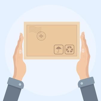 Kurierskie ręce trzymają paczkę. dostawa, pakowanie, transport. odbieraj, wysyłaj i przesyłaj produkty