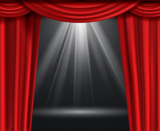 Kurtyna teatralna. luksusowe czerwone zasłony na czarnej ciemnej scenie rozrywkowej z reflektorem