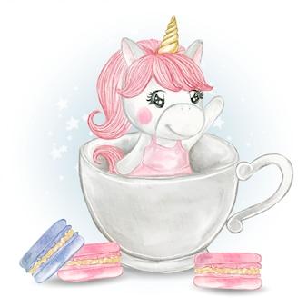 Ładna dziewczyna jednorożca w szklance herbaty z macaron
