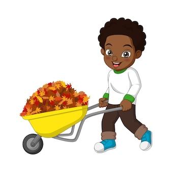Ładny afroamerykanin chłopiec pcha wózek z jesiennych liści