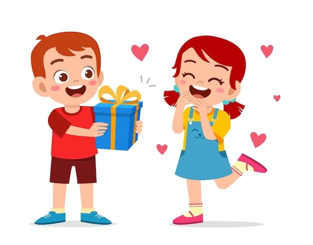 Ładny chłopak daje prezent małej dziewczynce.