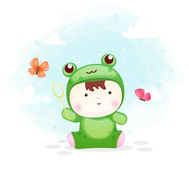 Ładny chłopczyk w stroju żaby łapiącego motyla