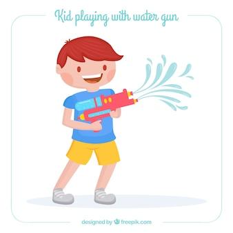 Ładny chłopiec bawi się pistoletem na wodę