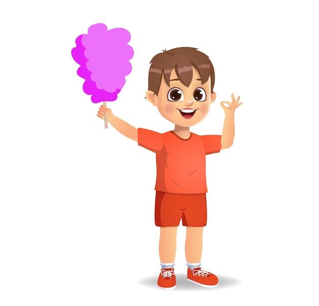 Ładny chłopiec dziecko jeść watę cukrową. odosobniony