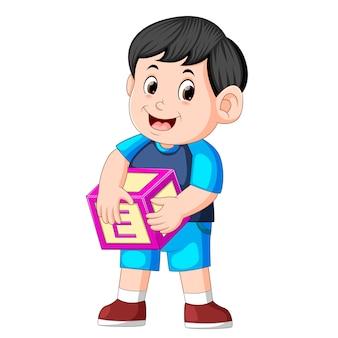 Ładny chłopiec trzyma kostkę alfabetu