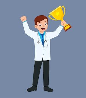 Ładny, dobrze wyglądający młody lekarz stojący i trzymając trofeum