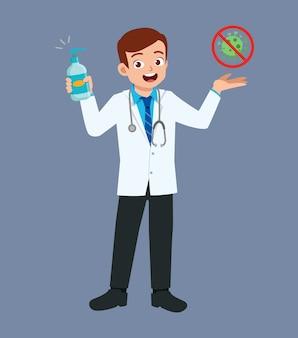 Ładny, dobrze wyglądający młody lekarz stojący i trzymający odkażacz do rąk