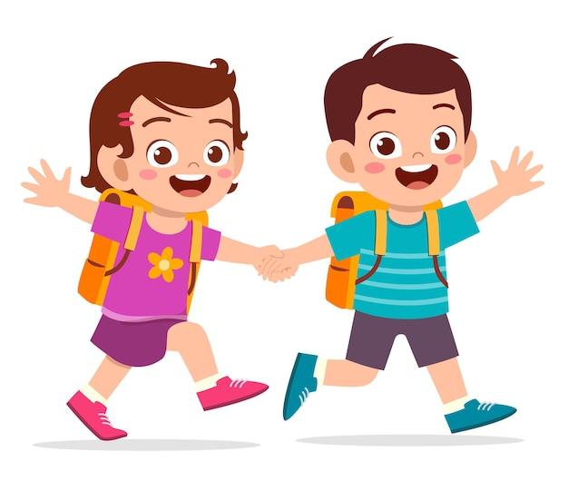Ładny dzieciak chłopiec i dziewczynka trzymając się za rękę i razem chodzą do szkoły