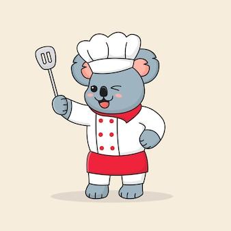 Ładny kucharz koala trzyma łopatkę i nosi kapelusz