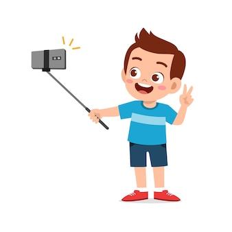 Ładny mały chłopiec dziecko poza i selfie przed kamerą