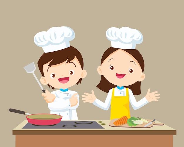 Ładny mały chłopiec szef kuchni i dziewczyna