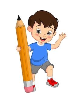 Ładny mały chłopiec trzyma duży ołówek