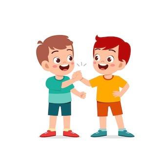 Ładny mały chłopiec trzymając rękę z przyjacielem