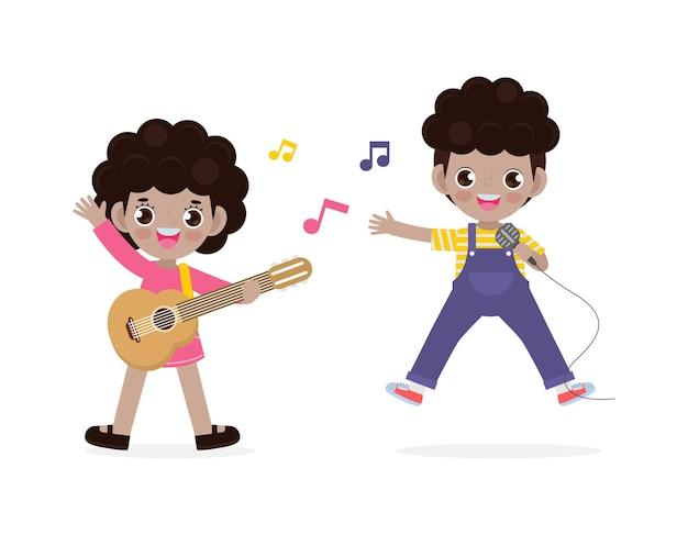 Ładny mały czarny chłopiec i dziewczynka gra na gitarze i śpiewa