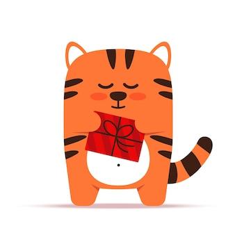Ładny mały pomarańczowy kot tygrysa w stylu płaski. zwierzę stoi z prezentem w pudełku. wszystkiego najlepszego i życzenia świąteczne.