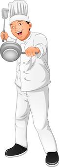 Ładny młody szef kuchni trzyma saute widelec i patelnię