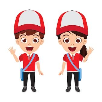 Ładny piękny dzieciak dostawy chłopiec i dziewczynka stojąc i machając z dostawy stroje i czapkę i torbę na białym tle