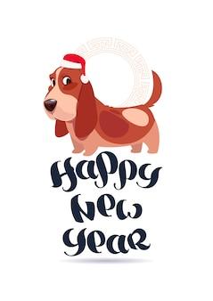 Ładny pies basset w santa hat na kartkę z życzeniami szczęśliwego nowego roku wakacje napis transparent