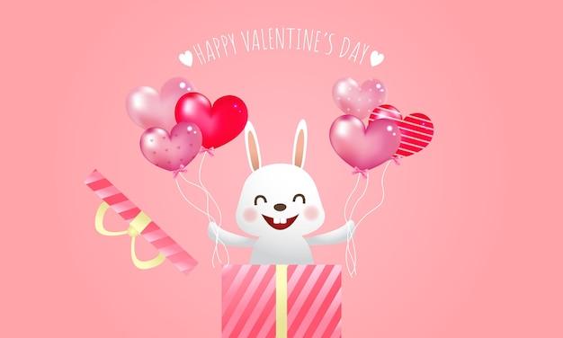 Ładny uśmiechnięty króliczek trzymając w obu rękach balony w kształcie serca. pozdrowienia walentynkowe. koncepcja pudełko prezent niespodzianka.